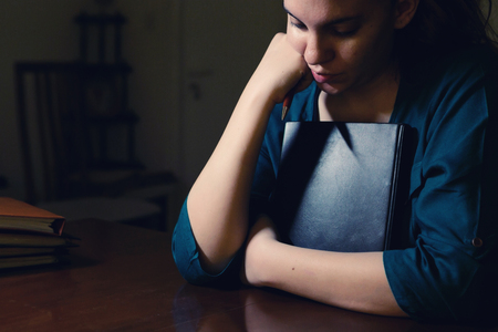 discouraged: Young lady in her office thinking late at night
