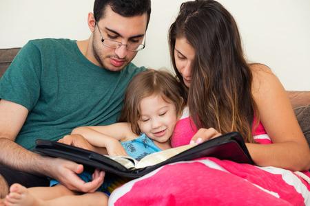 historias biblicas: familia joven que estudia la Palabra de Dios Foto de archivo