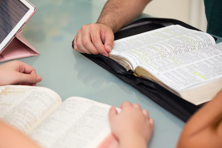 Close-up of People Reading the Word of God together photo