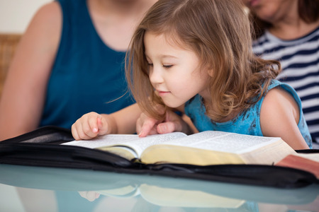 word of god: Young family studying the Word of God