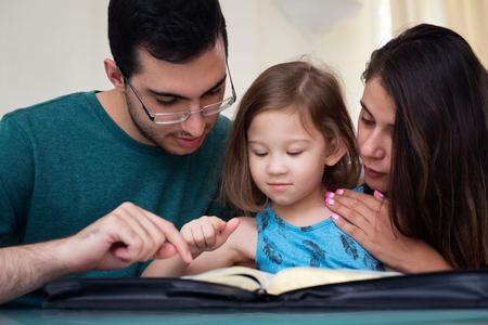 familia joven que estudia la Palabra de Dios Foto de archivo