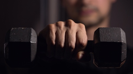 Young Man Holding Up Weight Towards Camera In The Gym