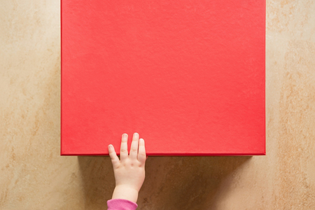 Cute Baby Hand On A Red Gift Box Stock Photo