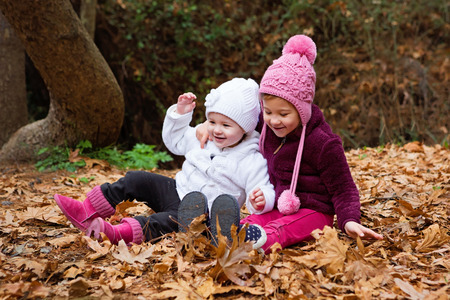 Cute Children Enjoying The Fall Leaves In Nature photo