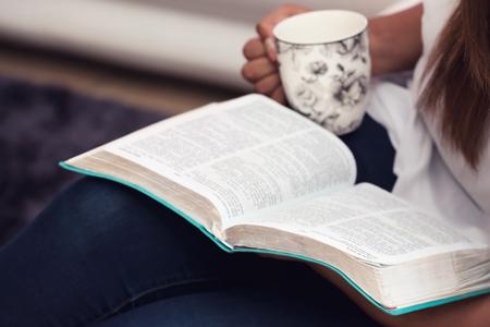 그녀의 킹 제임스 성경 공부 하 고 커피를 마시는 소녀를 닫습니다 스톡 콘텐츠