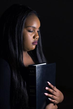 Perseguitata ragazza che tiene la sua Bibbia nel buio Archivio Fotografico - 88330693