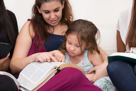 Women Studying The Word Of God With Child