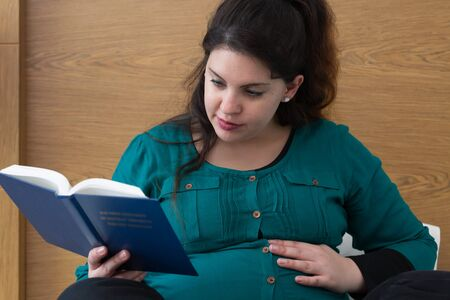 Young expectant mom reading her Bible in the morning Archivio Fotografico - 125829284