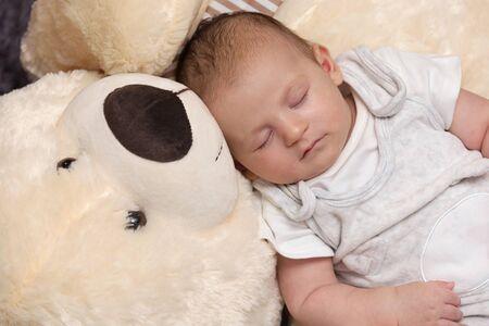 Friedliches Neugeborenes schläft mit riesigem flauschigen Teddybären