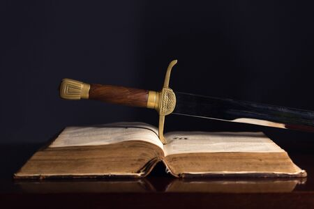 Ancient sword beside an open 150 Year Old Bible Foto de archivo