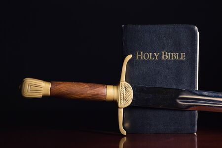 Old long sword beside the Holy Bible