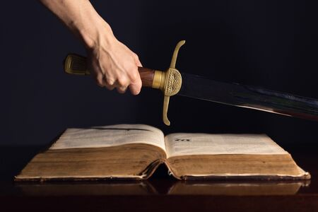 Strong male hand with sword on top of open Bible Stock fotó