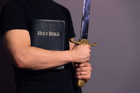Casually dressed strong young guy standing ready with his Bible and sword