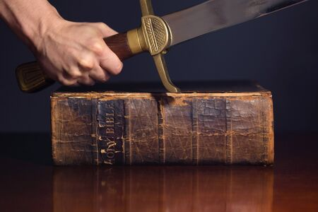 Strong male hand with sword and Bible