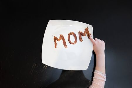 The word mom written on a plate with chocolate spread by her young daughter Фото со стока - 147433086