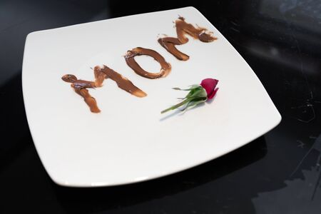 The word mom written on a plate with chocolate spread by her young daughter Фото со стока