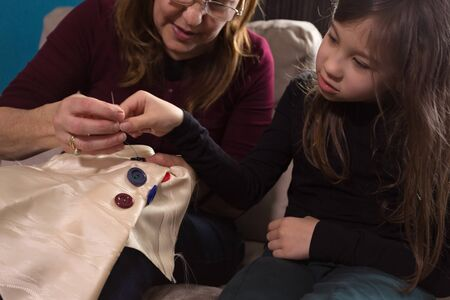 Loving Grandmother teaches her little granddaughter how to sew buttons