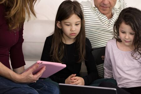 Family teaching children at home on Electronic Devices