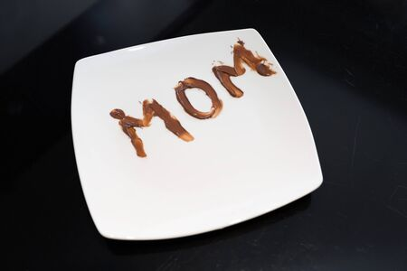 The word mom written on a plate with chocolate spread by her young daughter Фото со стока - 147433150