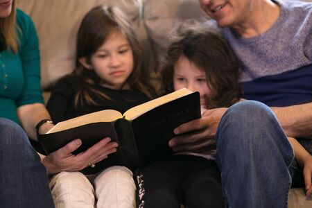 Grandparents teaching grandchildren about the Holy Bible 스톡 콘텐츠