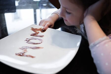 The word mom written on a plate with chocolate spread by her young daughter Фото со стока - 147433158