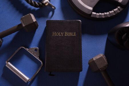 Holy Bible surrounded by dumbbells weights and other exercise equipment 写真素材