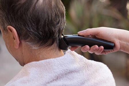 Family member cutting mans hair at home
