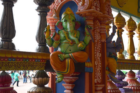 A small Hindu worship place decorated with stunningly vibrant colorful Dravidian architecture elephant, deity statues, pillars at Batu Caves Stock Photo