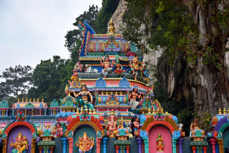 A small Hindu worship place decorated with stunningly vibrant colorful Dravidian architecture elephant, deity statues, pillars at Batu Caves