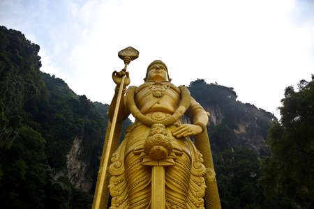 Gombak, Selangor, Malaysia 08.14.2019: Upper body part of the giant and amazingly detailed golden Murugan statue with the famous limestone hill of Batu Caves and bright sky in the background