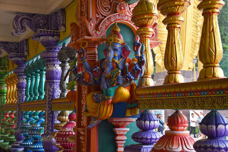 Gombak, Selangor, Malaysia 08.14.2019: A small Hindu worship place decorated with stunningly vibrant colorful Dravidian architecture elephant, deity statues, pillars at Batu Caves