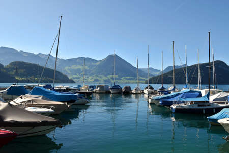 Vitznau, Switzerland 29.09.2019: Sailing boats resting in the port of Vitznau on Lake Lucerne with view of mountain ranges