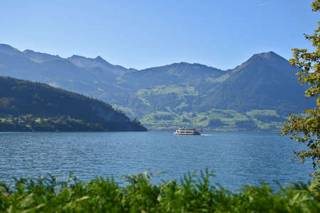 Landscape view of Lake Lucerne with the majestic Mount Pilatus and valleys in the background while a steamboat is crossing the shores