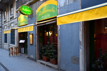 Milan, Italy, 08.04.2019: Entrance, front with two bar stools of the famous, traditional Italian Restaurant and Pizzeria Bellavista on Broletto street