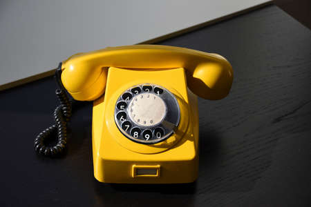 Old Retro Vintage Yellow Rotary Telephone on black wood table