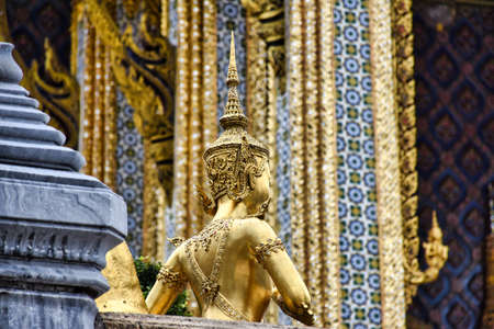 Beautifully stunning gold statue of a Kinnara, a beloved mythical half-human, half-bird creature on the Upper Terrace of Wat Phra Kaew or Temple of the Emerald Buddha in the Grand Palace of Bangkok