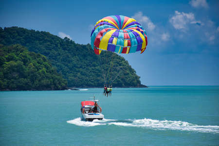 Parasailing on the waves of the azure Andaman sea under the blue sky near the shores of the sandy beautiful exotic and stunning Cenang beach in Langkawi island, in Malaysia.