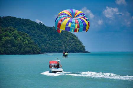 Parasailing sulle onde dell'azzurro mare delle Andamane sotto il cielo blu vicino alle rive della bellissima spiaggia sabbiosa esotica e mozzafiato di Cenang nell'isola di Langkawi, in Malesia.