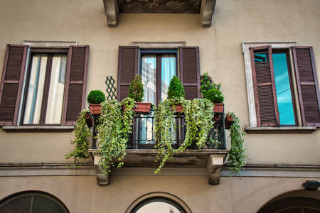 Milan, Italy 05.12.2020: An old traditional italian balcony with green plants on it 写真素材