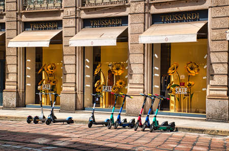 Milan, Italy 08.08.2020: Electric scooters parking in front of the displays of a Trussardi store in downtown Milan