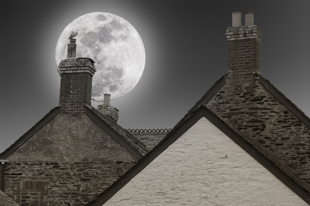 sloping: Full moon over the chimneys of the houses