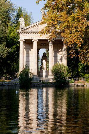 esculapio: El Templo de Esculapio se refleja en el lago en Villa Borghese Foto de archivo