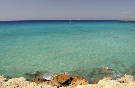 ranging: The image shows the gradient of colors on the sea of Formentera ranging from brown of the rocks to blue horizon