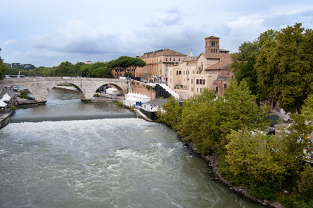 swells: View of the island and bridge of Cestius while on the Tiber rain swells the river rapids Stock Photo