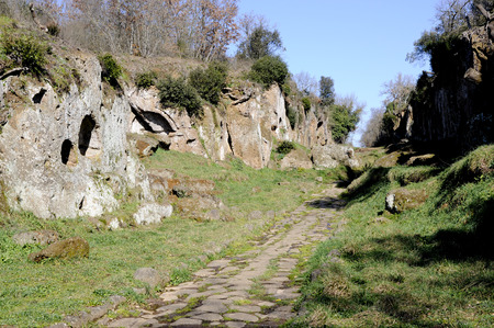 flanked: The ancient Roman road Amerina flanked by the remains of Etruscan tombs. This road linked the city of Rome and Umbria.