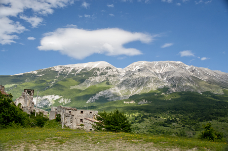 resisting: View of the mountains of Maiella from Roccacaramanico near some ruined and abandoned houses Stock Photo