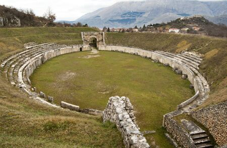 medioeval: View of ancient Roman Amphitheater at Alba Fucens, Italy, dating the first half of the first century AD, with the ruined medioeval village and castle on the top background. Editorial