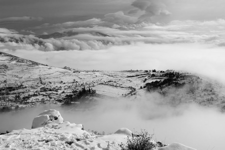 Snowy landscape in a partly cloudy with fogs