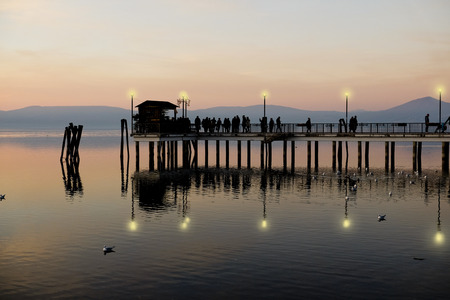 Crowded pier at evening at Anguillara Sabazia harbour, Rome, Italy