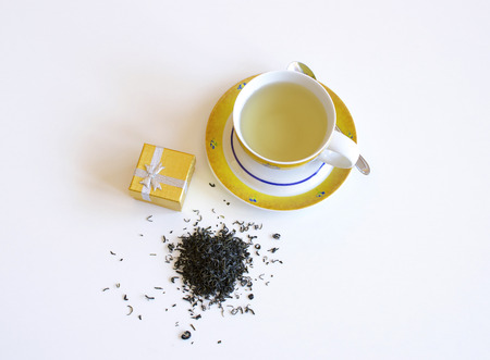 Yellow porcelain cup of tea with blue flowers, teaspoon, spill tea leaves on a white background